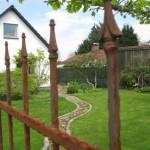 Naturstein Weg mit rostigem Tor