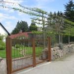 Tilia Spalier Linden, Natursteinmauer mit rostigem Tor