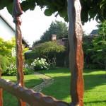 Naturstein Weg mit rostigem Tor, Hydrangea Annabell ( Hortensie)